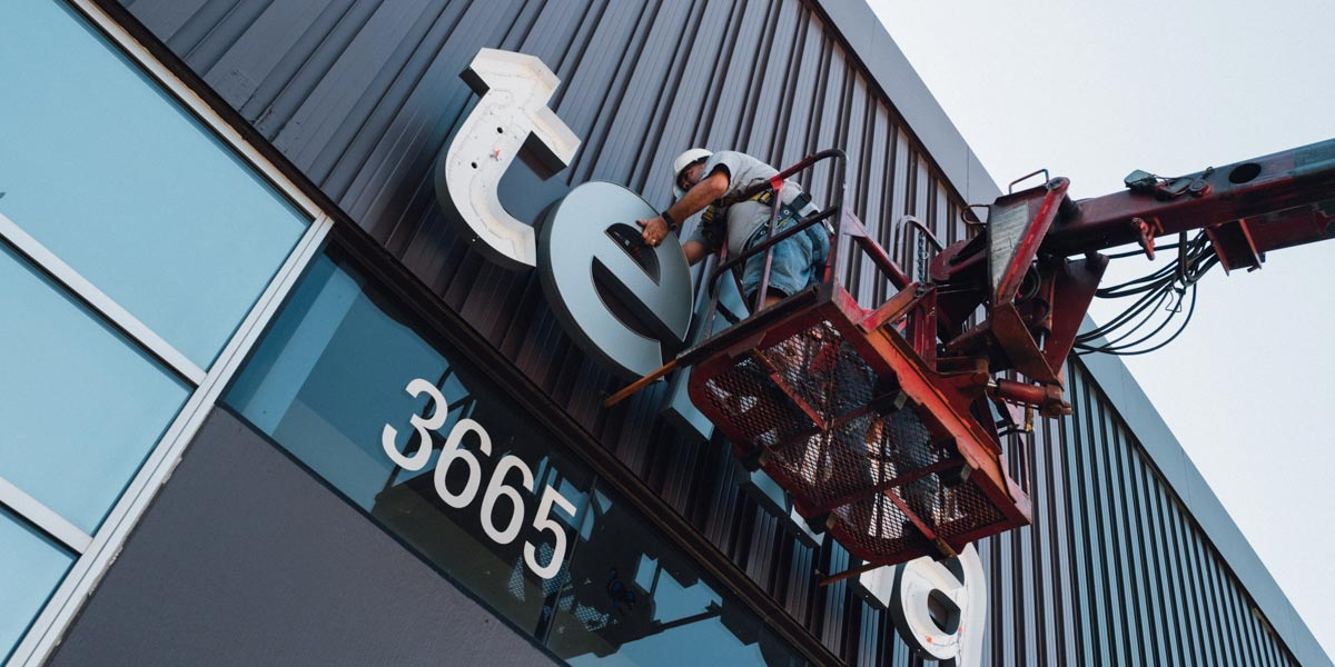 The Tekna sign being put on a building